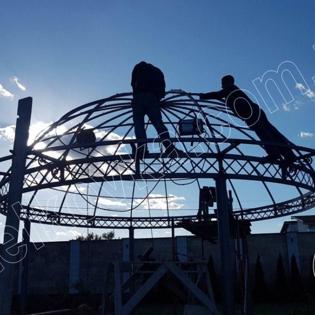 Installing the roof of a wrought-iron gazebo